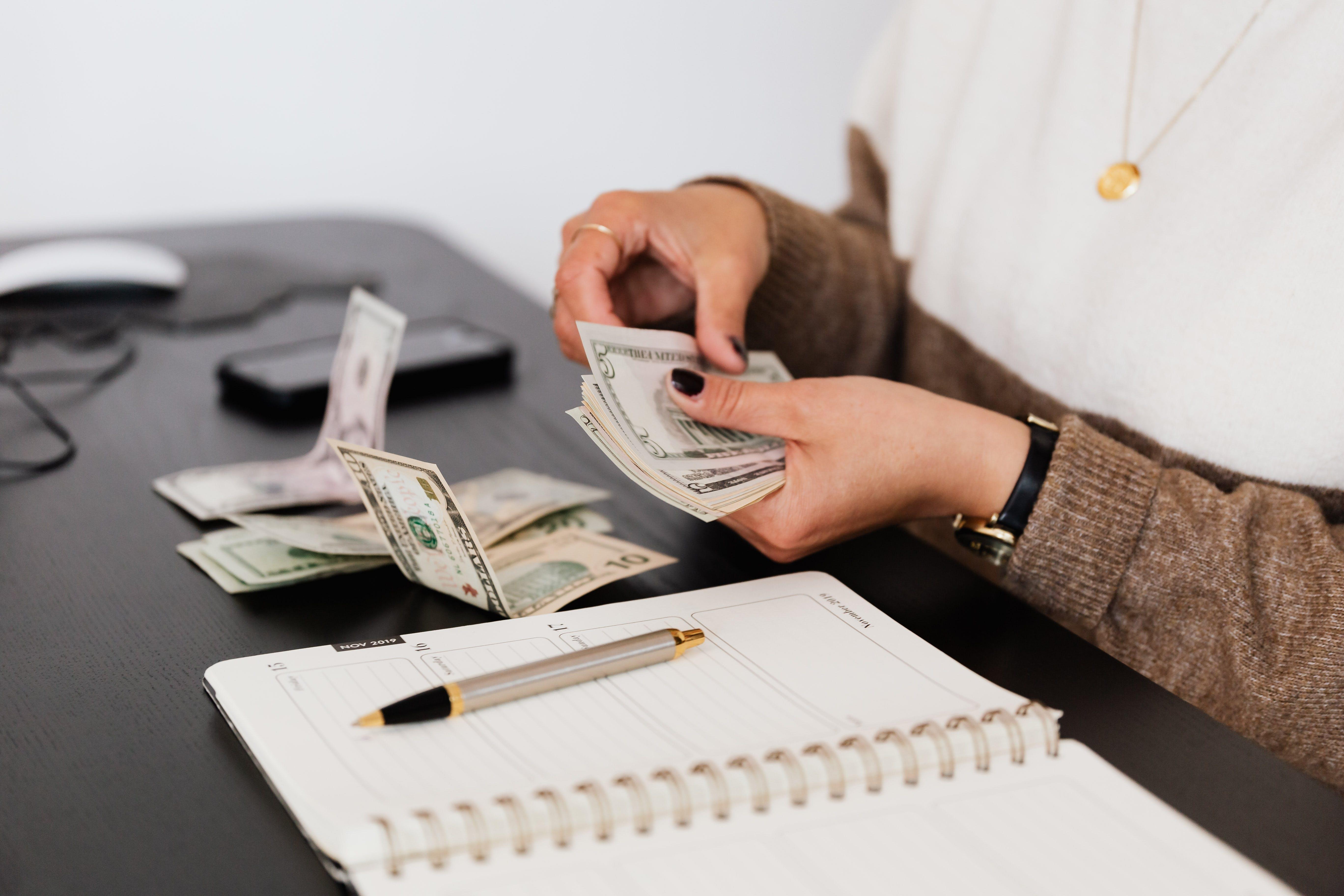 Gewas salarisbediende telt geld terwijl hij aan tafel zit